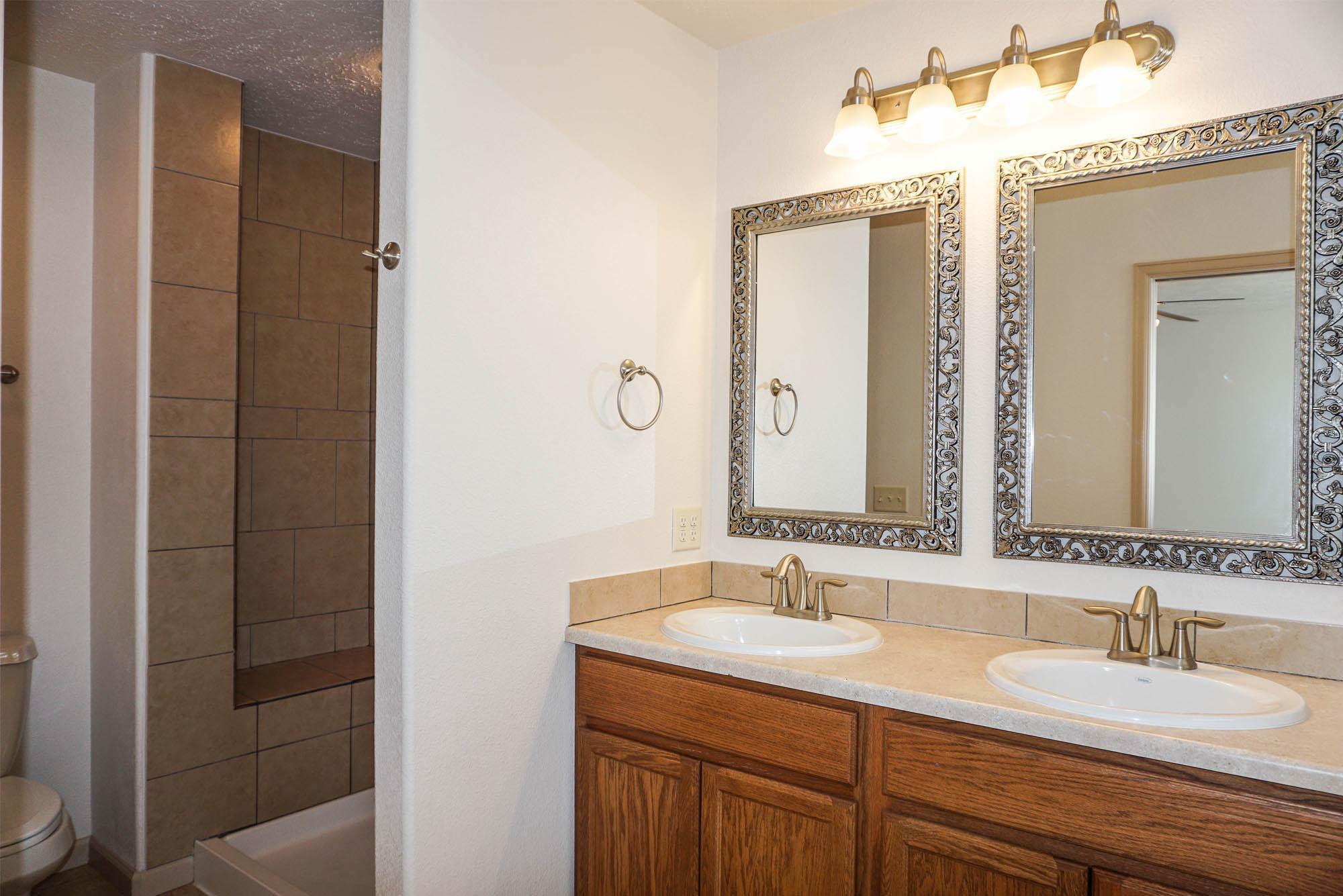 161 Sun Hawk master bath with double vanities & step-in shower