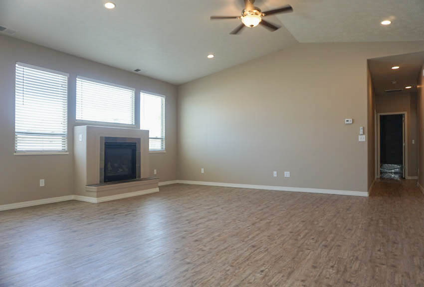 Living room has a lighted ceiling fan with a remote, gas fireplace, and large windows to let in natural light.