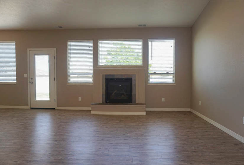 Large windows frame the gas fireplace with custom tiled hearth