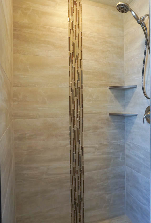 Master Shower in 188 Night Hawk - a step-in shower with custom tile work, corner shelves, & shower head with hose attachment.