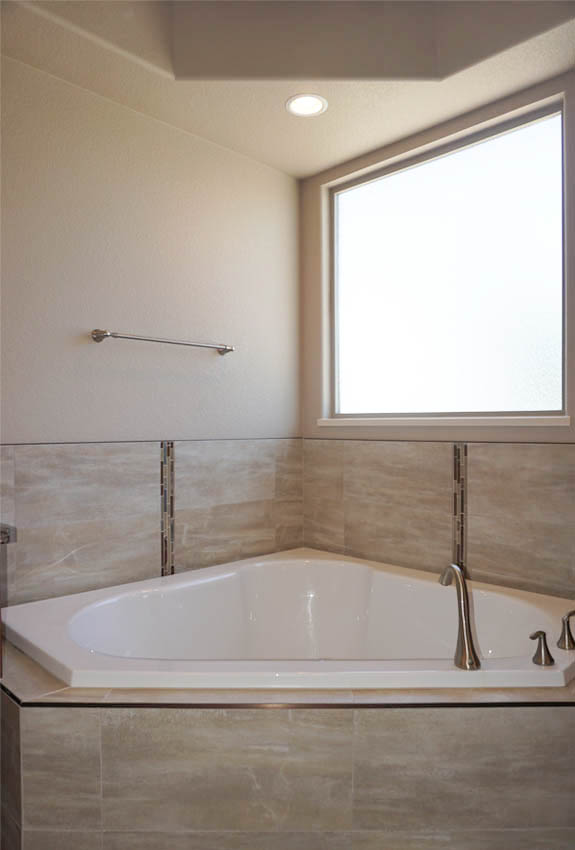 Corner soaking tub has a window with privacy glass to let in natural light, but maintain your privacy.