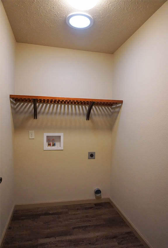 The laundry room has a shelf over the washer/dryer area