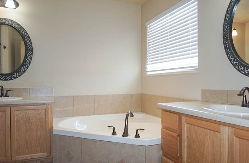 The master bath includes double vanities flanking a corner soaking tub.