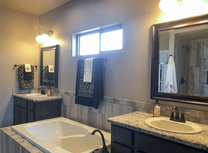 The master bath of 1305 Niblick has separate vanities flanking the soaking tub, a semi-private toilet, and a roll-in shower with a bench.
