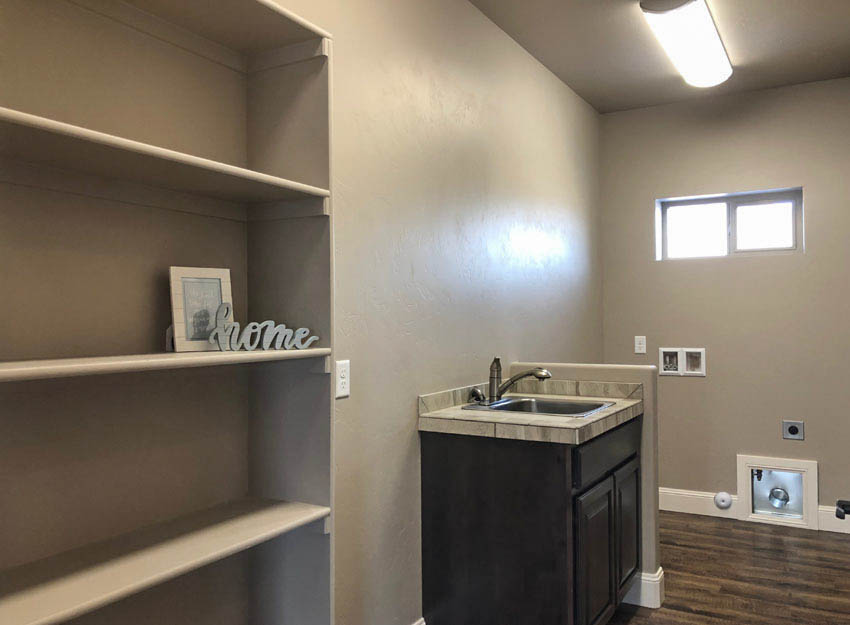The laundry room of 1305 Niblick Way has shelving, a storage vanity with a sink, and space for a washer and dryer.